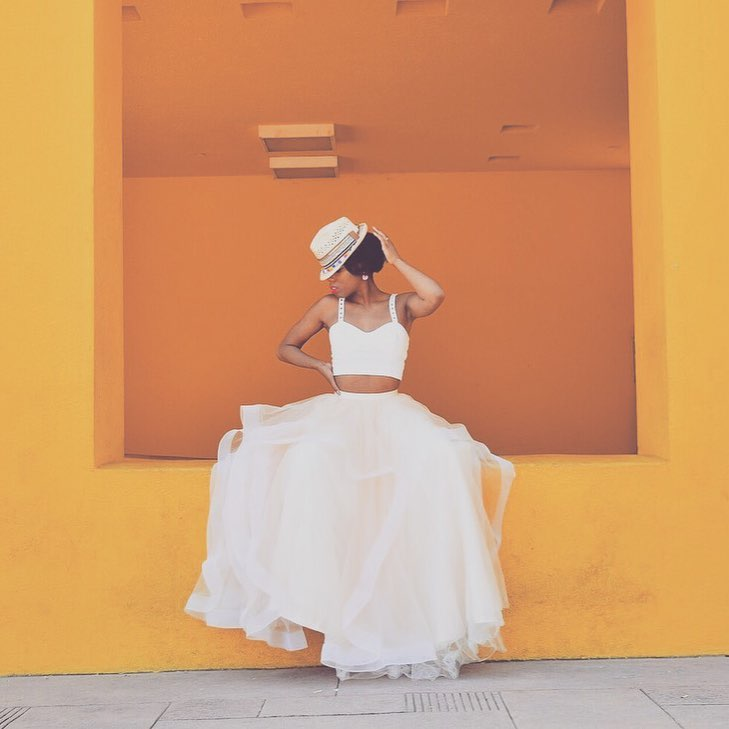 Woman in fedora sitting on yellow and orange wall in crop top wedding dress