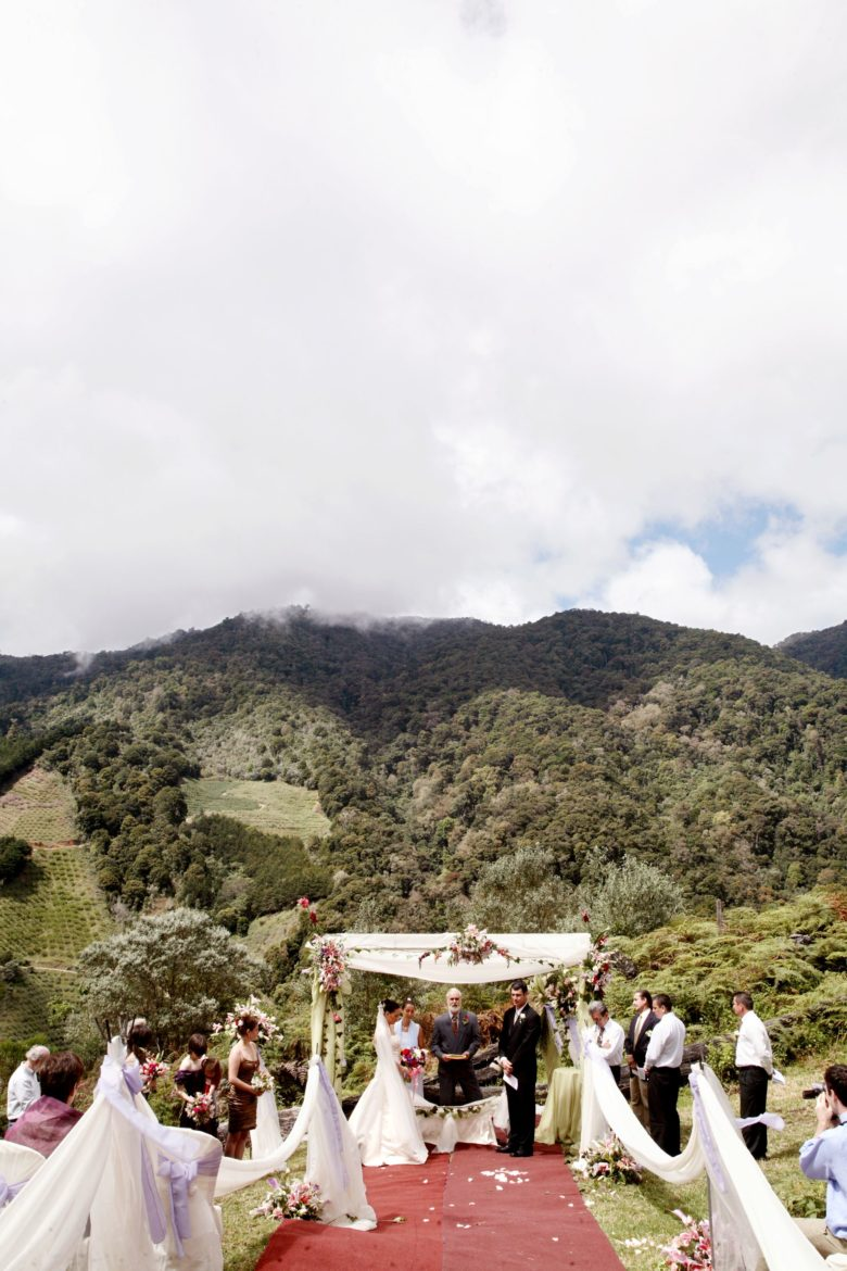 outdoor wedding ceremony under canopy, at base of green mountain