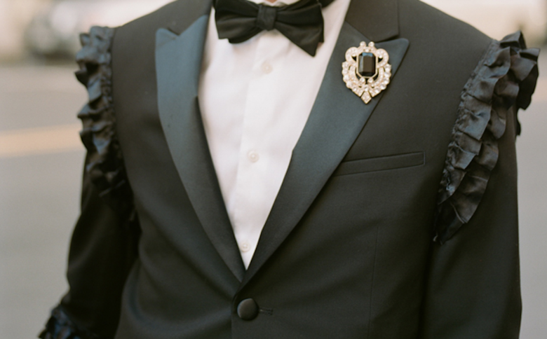 Tux jacket with shoulder seam ruffles and bejeweled broach