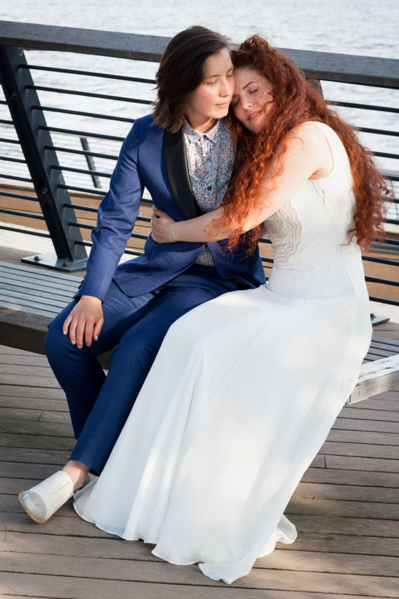 Couple in wedding attire embracing on bench near water