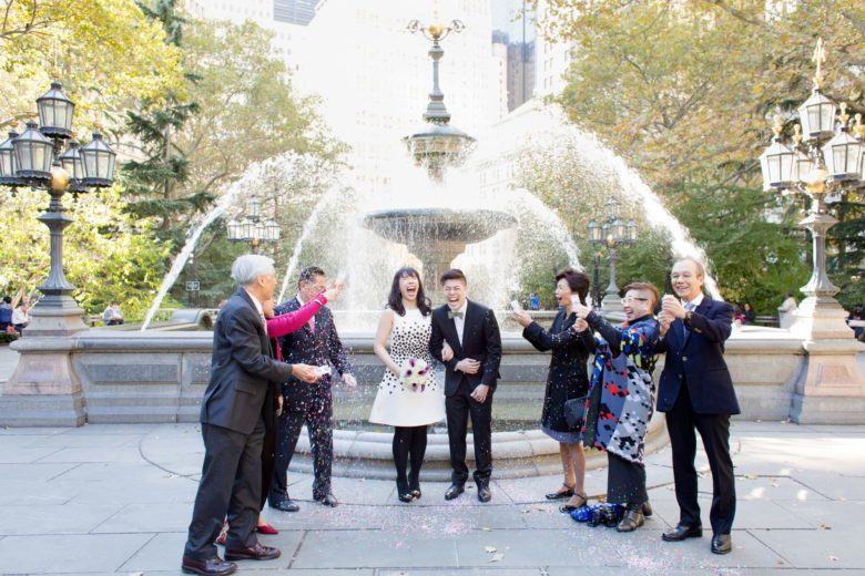 Couple, with their families, being showered in confetti in front of a fountain