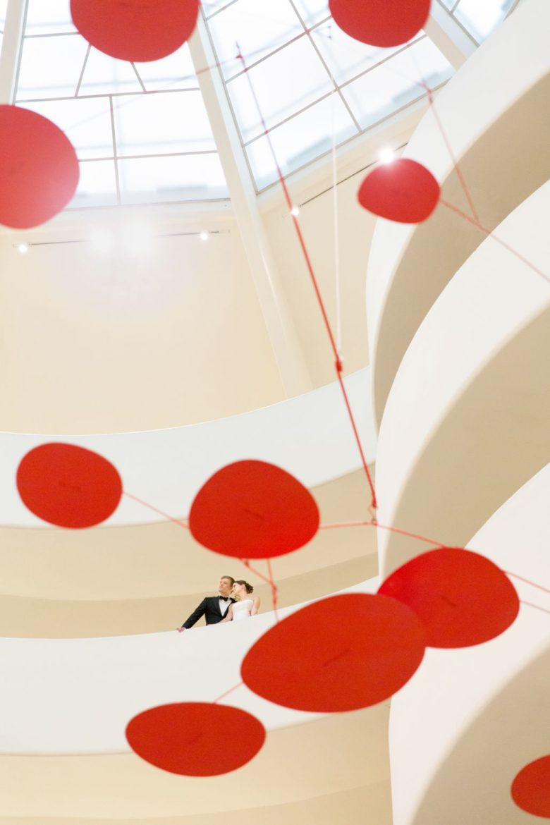 Bride and Groom in Guggenheim landing beyond Alexander Calder large red mobile