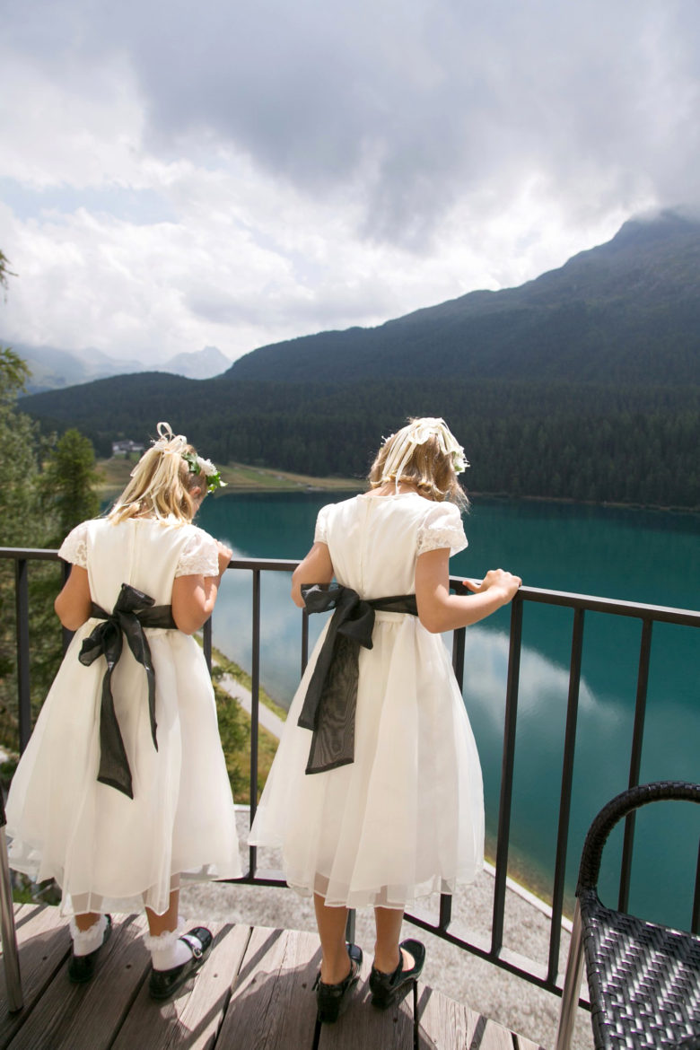 flower girls from behind, looking over balcony railing at blue water and a green mountain