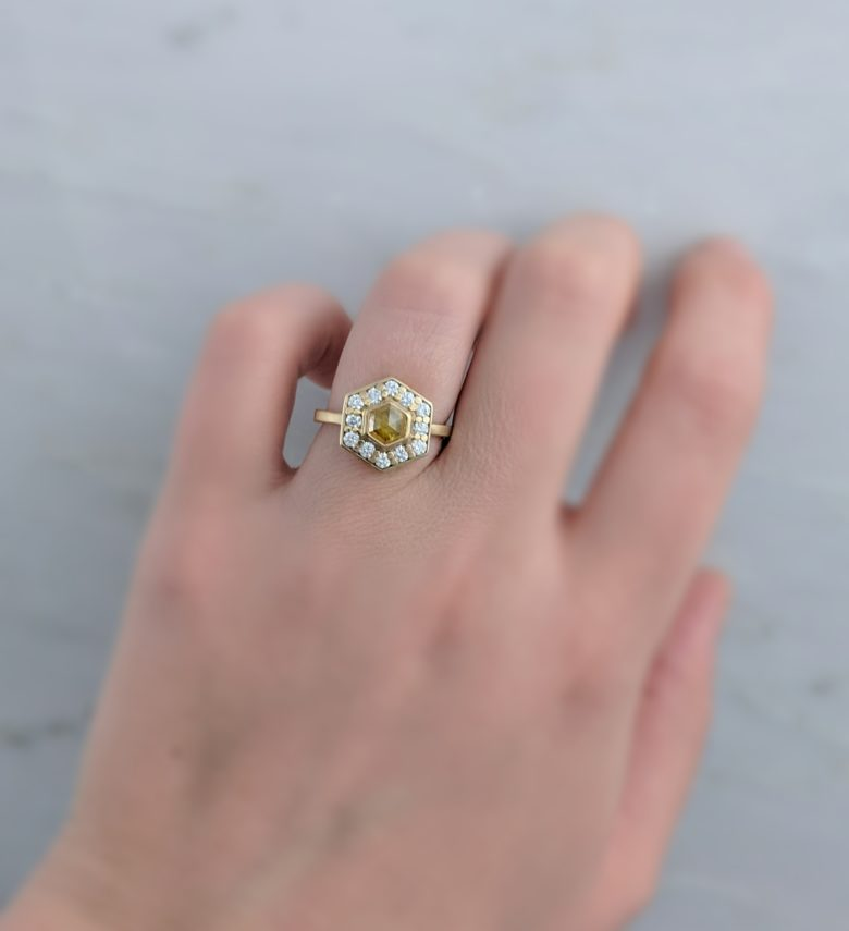 Hexagonal yellow gold ring with yellow stone surrounded by small diamonds on woman's ring finger