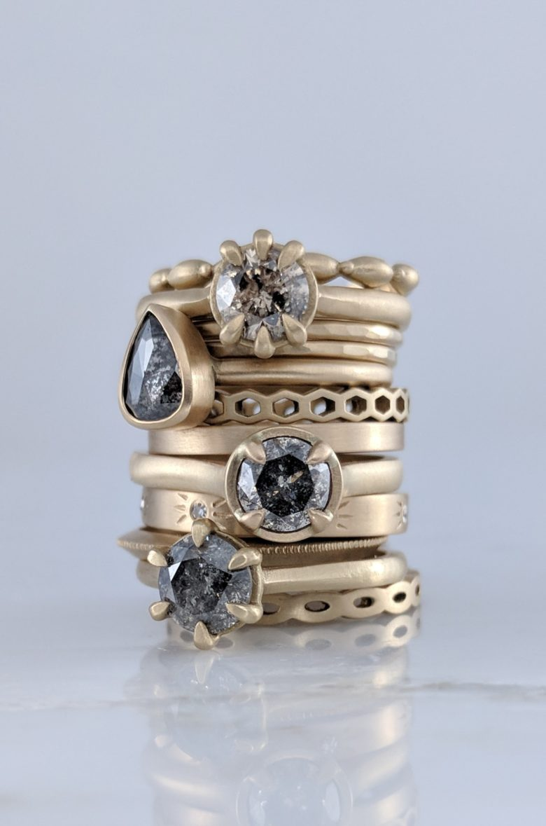 stack of rings, some with solitaire black and white speckled stones set in soft matte yellow gold